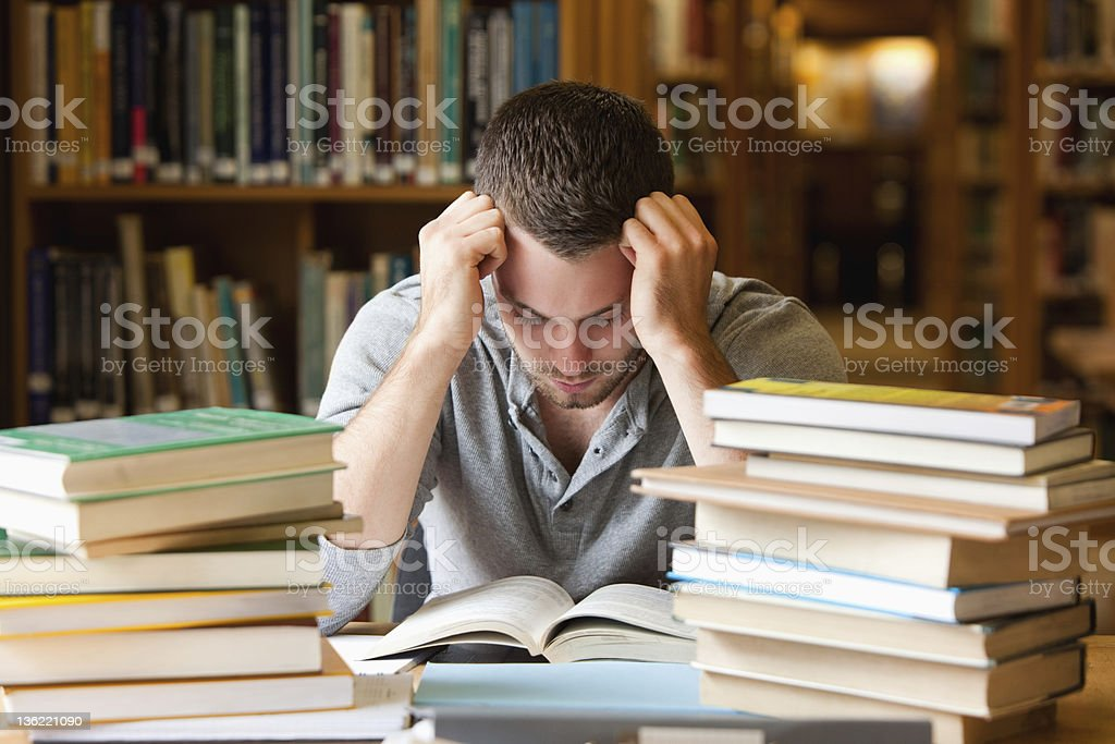 Tired student having a lot to read royalty-free stock photo