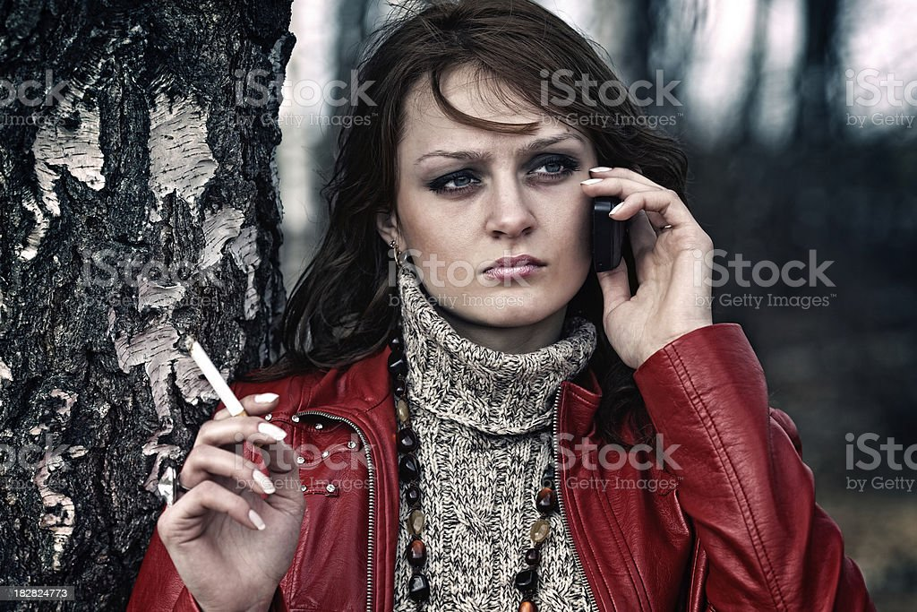 Tired unhappy woman smokes and talks on the phone royalty-free stock photo