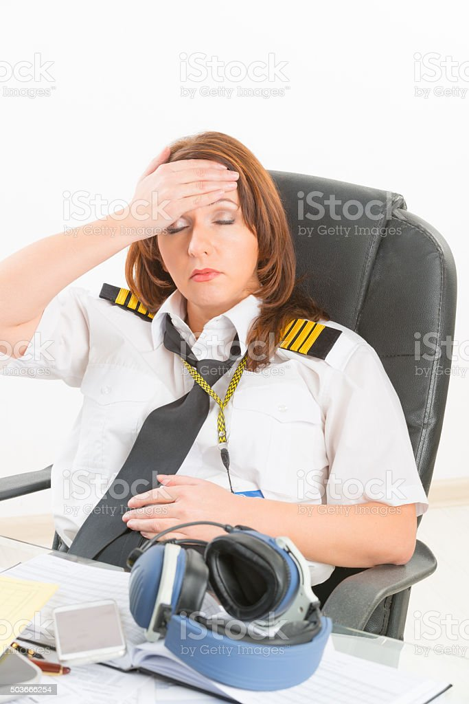 Tired woman airline pilot in the office stock photo