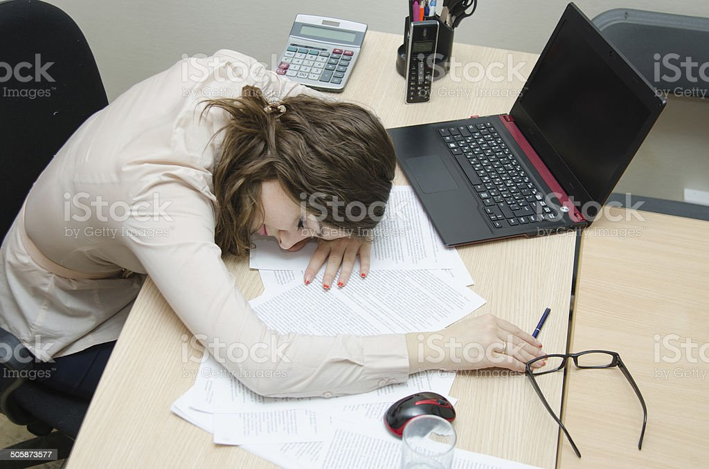 Tired woman asleep on a workplace at office stock photo