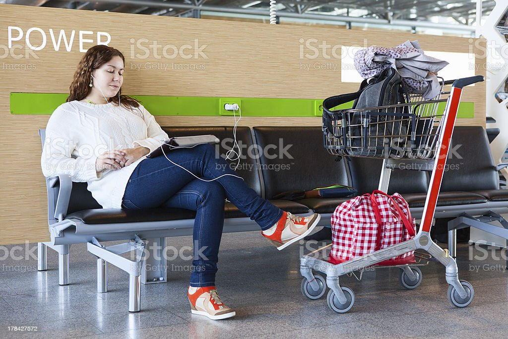 Tired woman charging tablet pc in airport lounge royalty-free stock photo