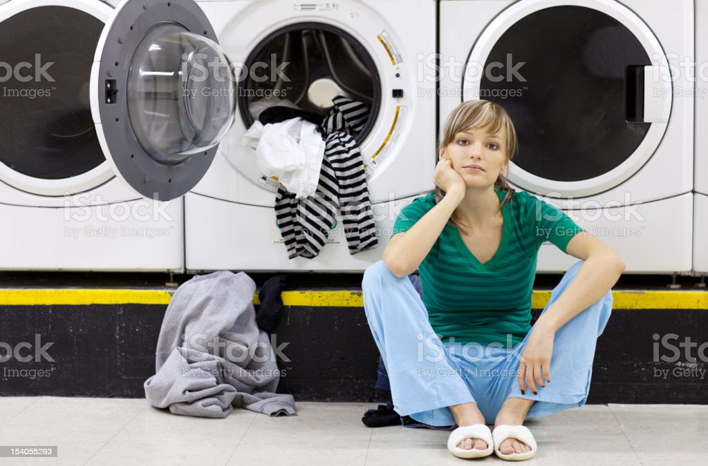 Tired woman doing laundry in laundromat royalty-free stock photo