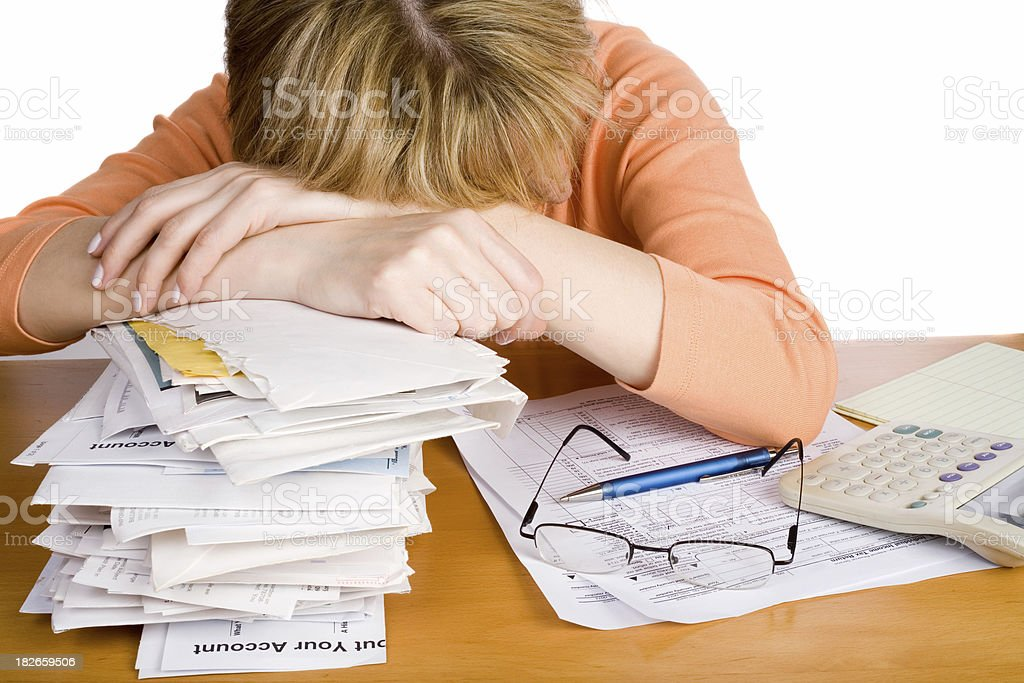 Tired woman in a heap of undone accounting report royalty-free stock photo