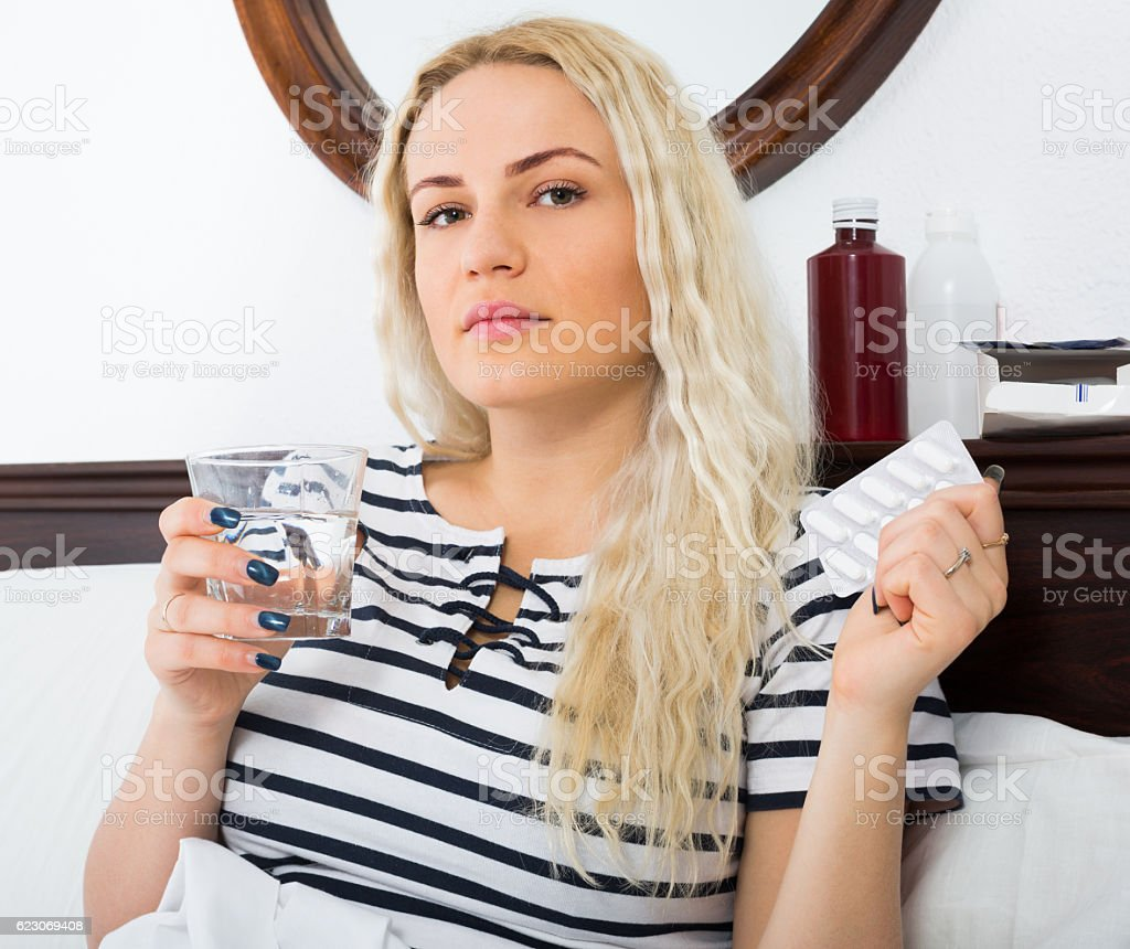 Tired woman in bed having heavy migraine stock photo