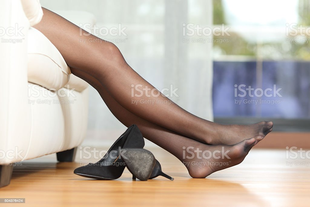 Tired woman legs resting on couch stock photo