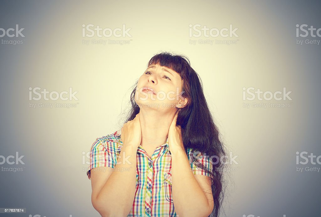 tired woman massaging her painful neck stock photo