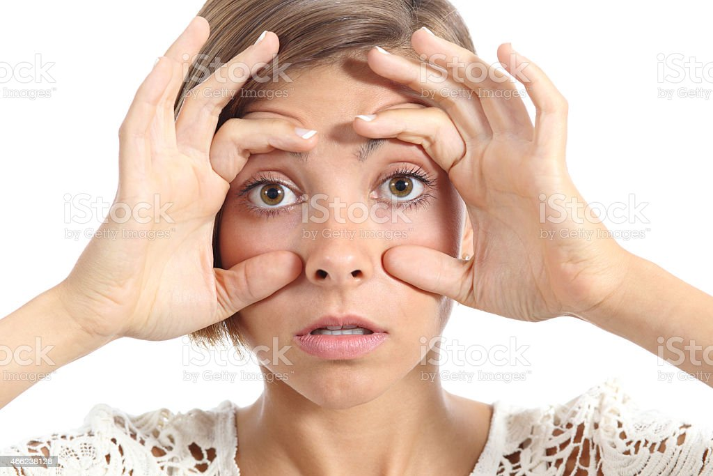 Tired woman opening her eyes with the fingers stock photo