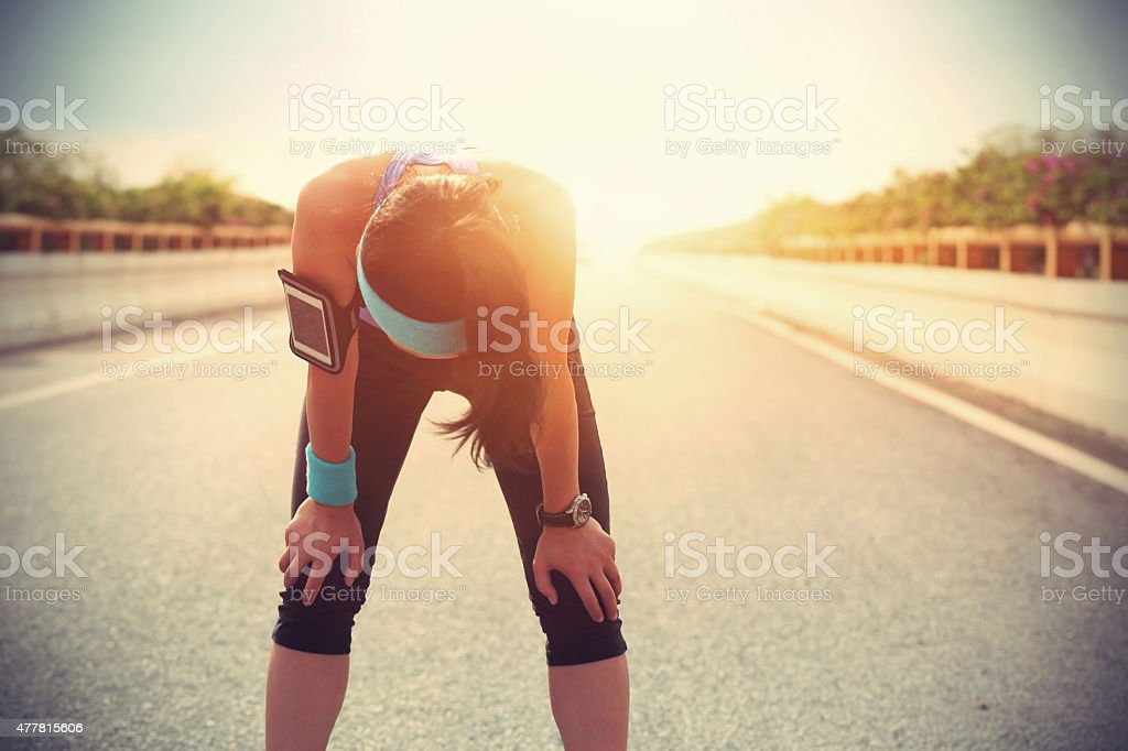 tired woman runner taking a rest after running hard stock photo