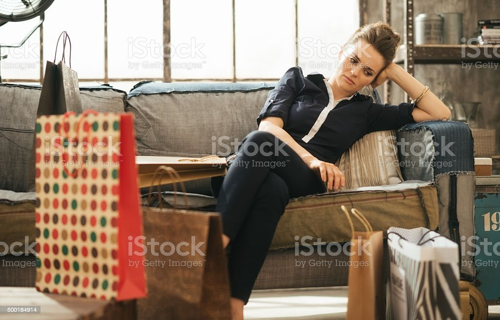 Tired woman sitting on couch among shopping bags in loft stock photo