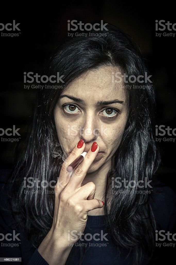 Tired woman smoking an electronic cigarette royalty-free stock photo