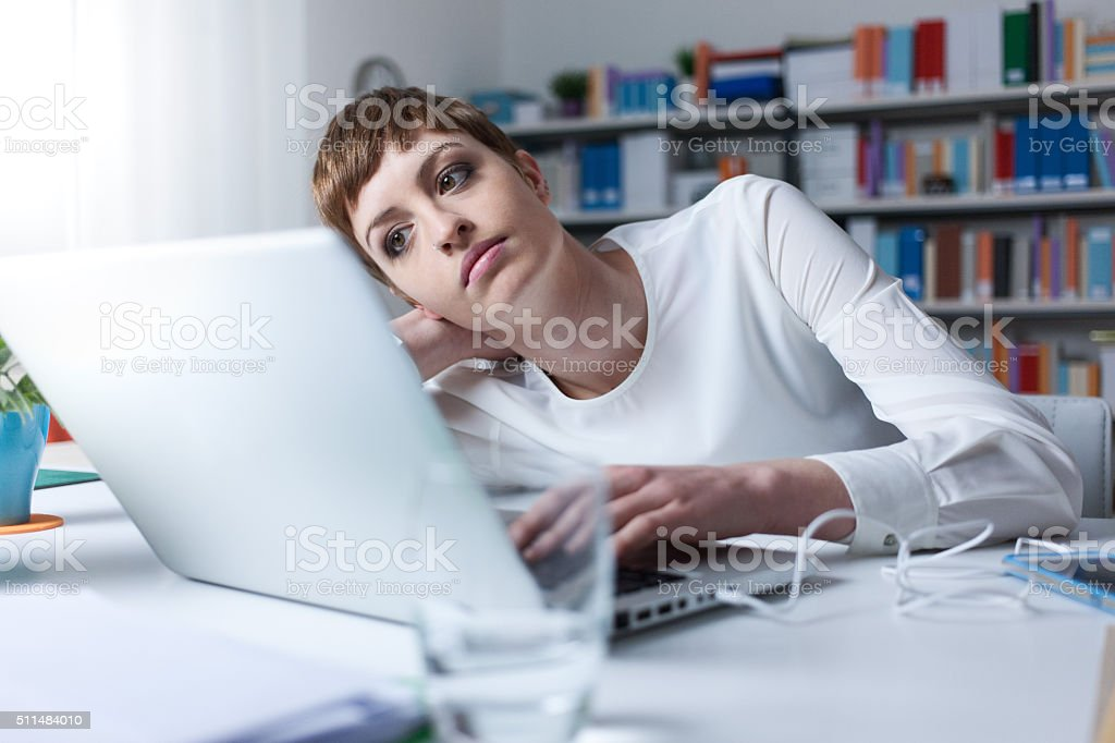 Tired woman using a laptop stock photo