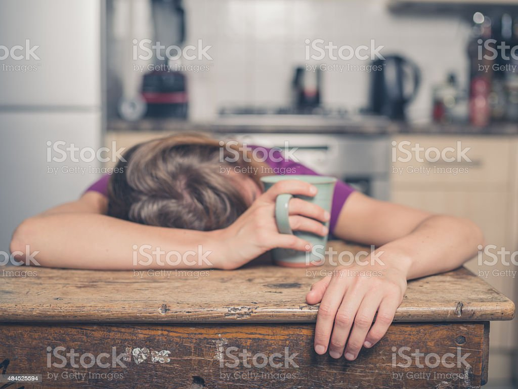 Tired woman with tea in kitchen stock photo