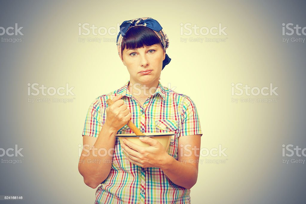 Tired woman with utensils in hand stock photo