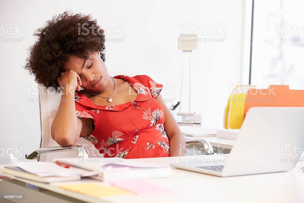 Tired Woman Working At Desk In Design Studio stock photo