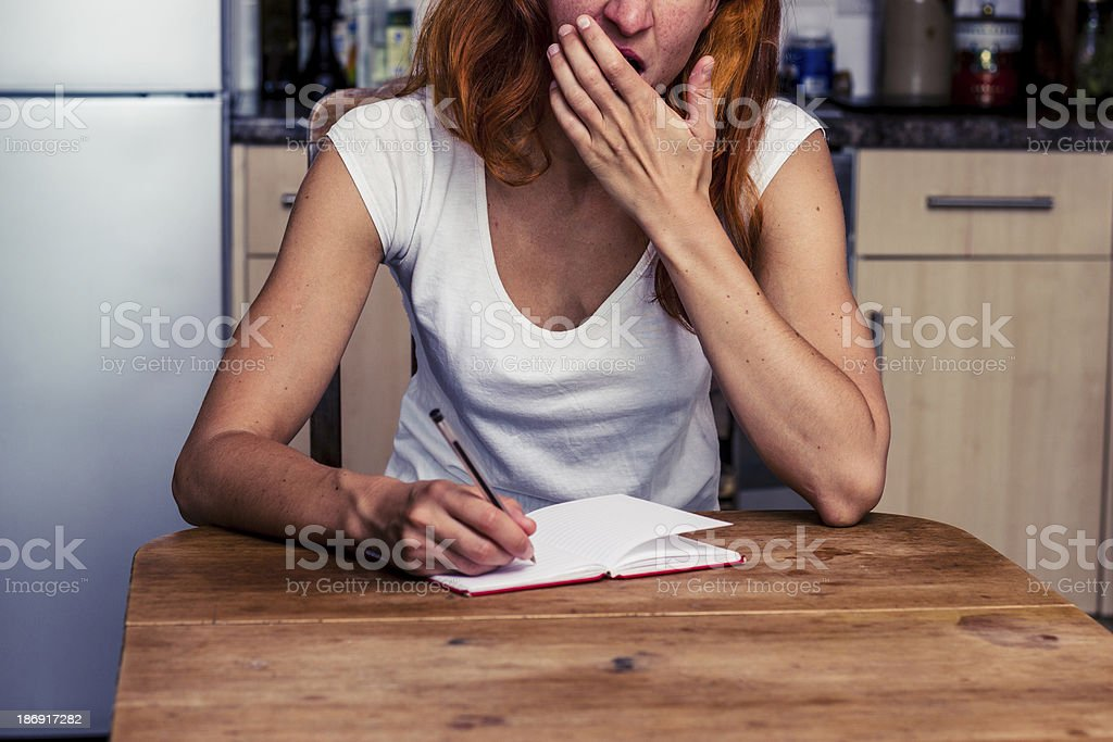 Tired woman writing in her kitchen royalty-free stock photo