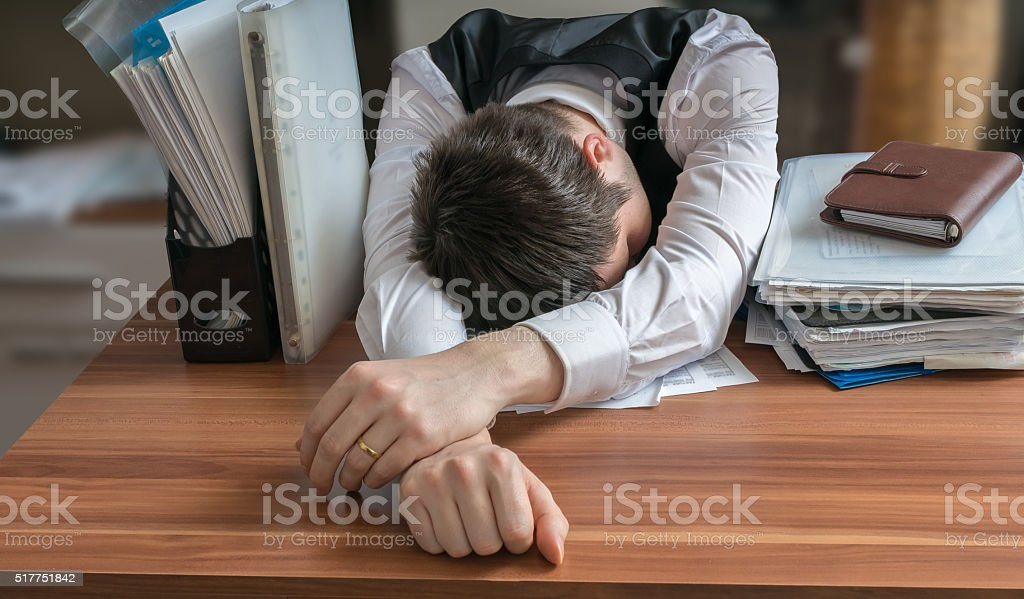 Tired workaholic is sleeping on desk in office. stock photo