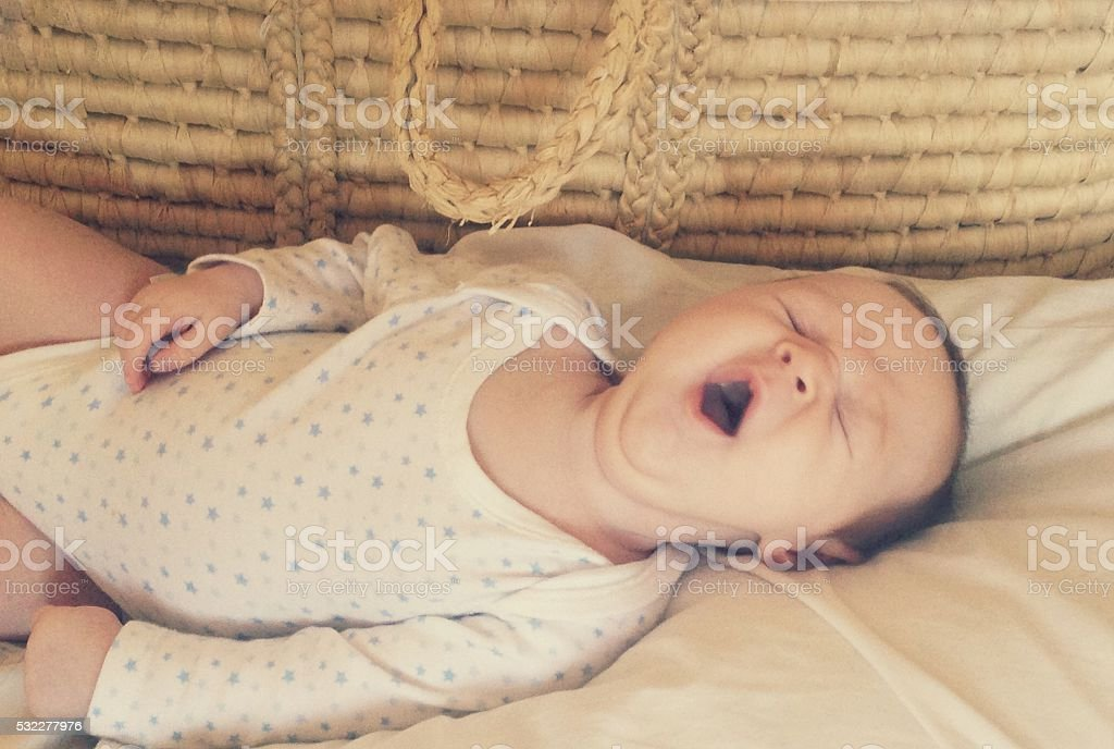 Tired yawning baby in his Moses basket stock photo