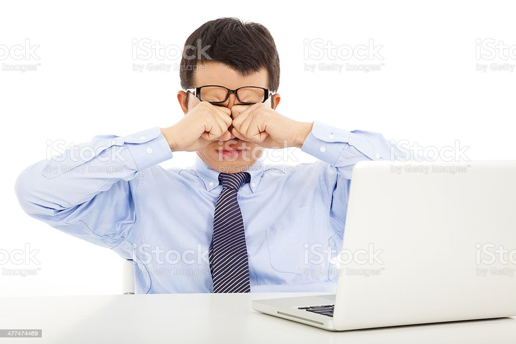 tired young businessman rubbing his eyes stock photo