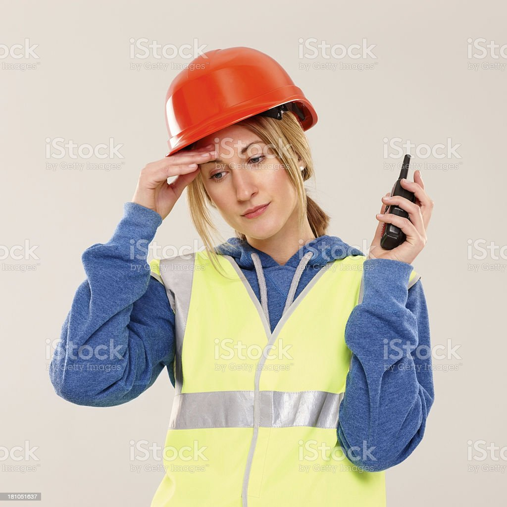 Tired young female construction worker with a cb radio royalty-free stock photo