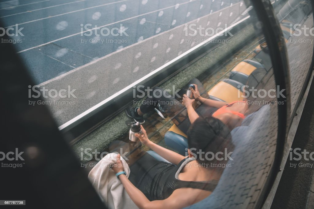 Tired young fitness women in sportswear resting in stadium seats stock photo