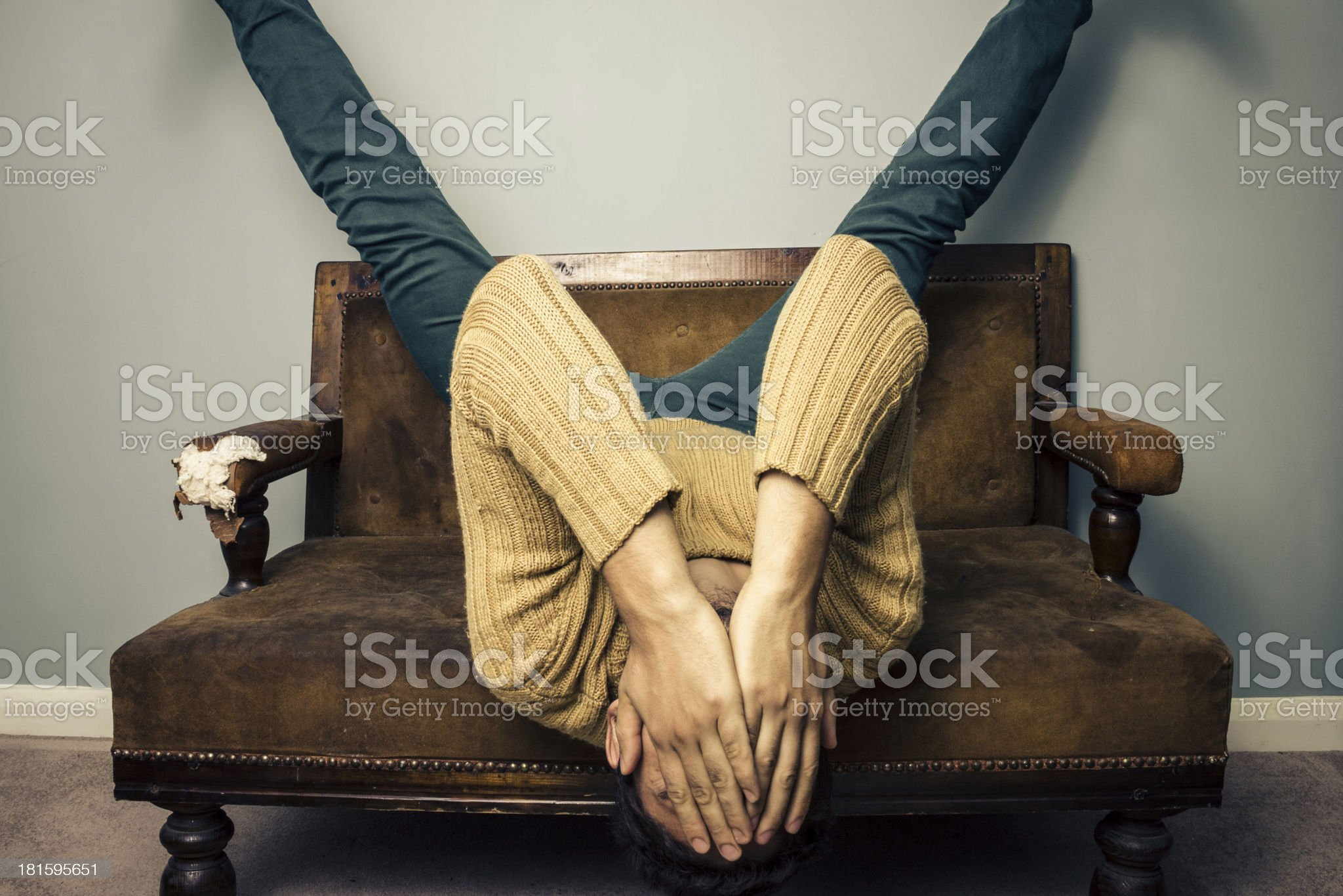 Tired young man is upside down on old sofa royalty-free stock photo