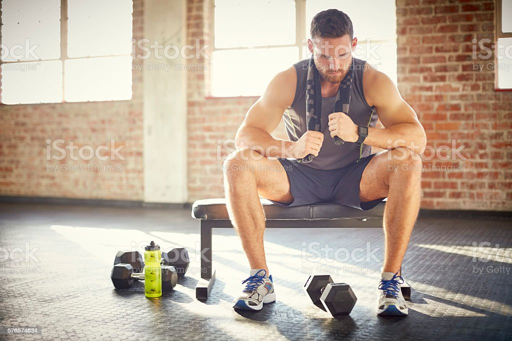 Tired young man sitting on bench in gym stock photo