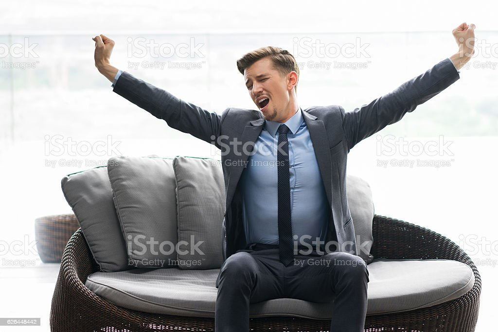 Tired Young Man Sitting on Couch and Yawning stock photo
