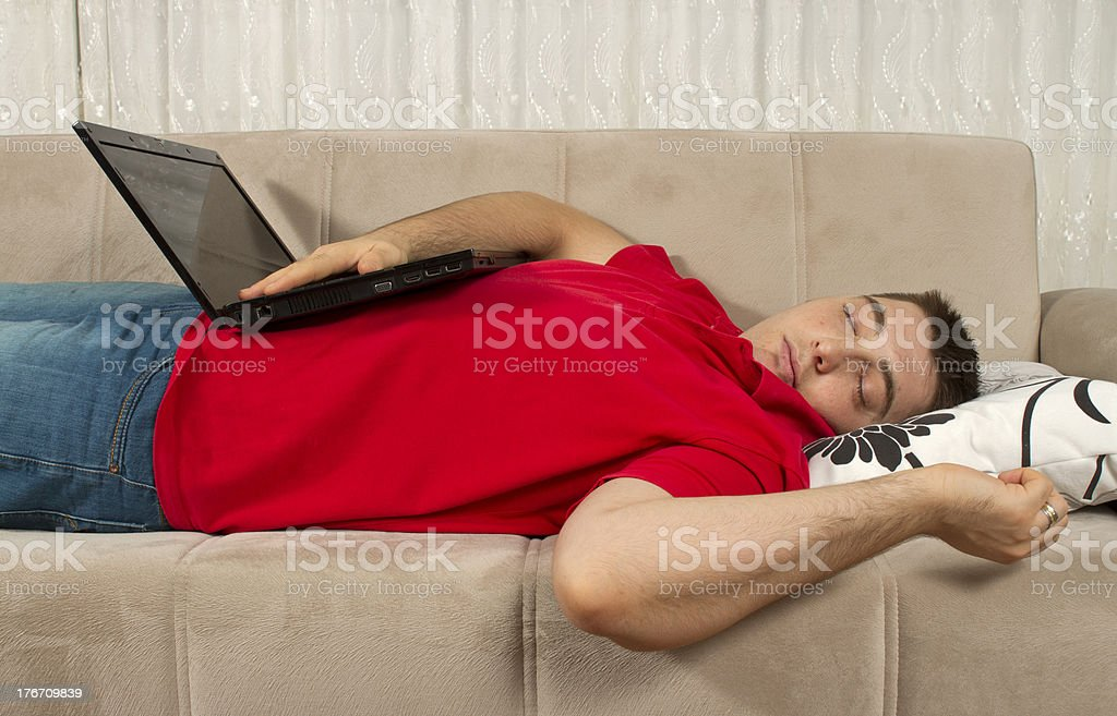 Tired Young Man Sleeping With Laptop On The Couch royalty-free stock photo