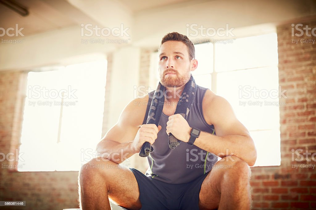 Tired young man with towel around neck in gym stock photo