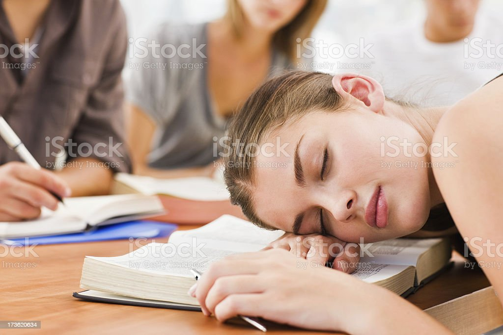 Tired young woman sleeping while studying royalty-free stock photo