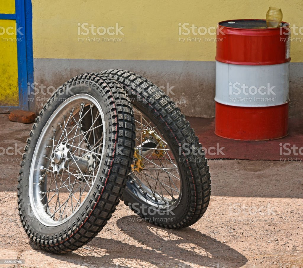 Tires of a speedway motorcycle and a fuel barrel stock photo