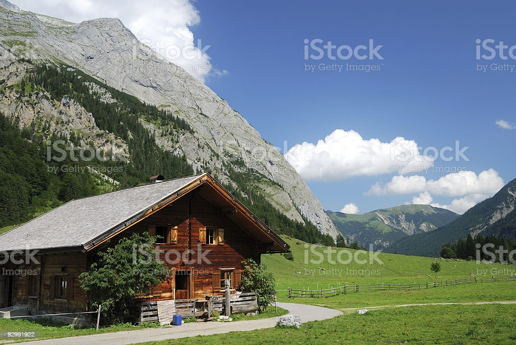 Tiroler Hut on a large pasture with mountain scape behind stock photo