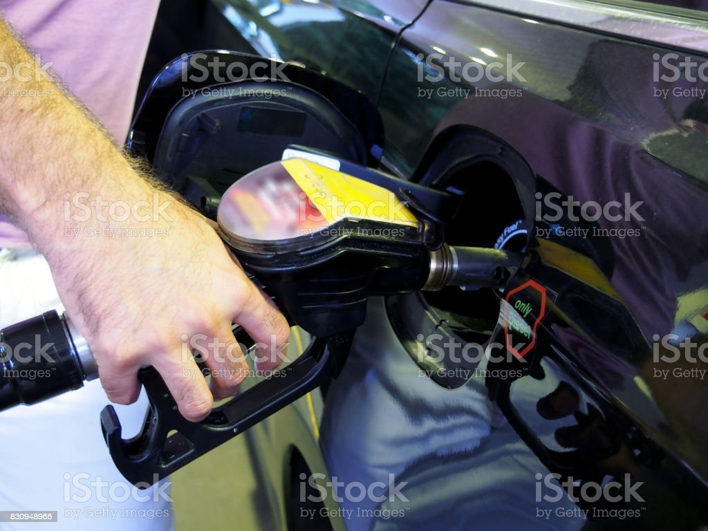 To get fuel from the fuel station to the car with the pump stock photo