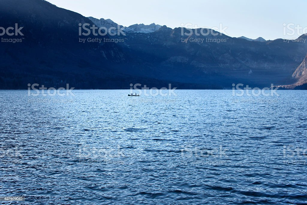 To paddle a boat on a lake in the mountains stock photo