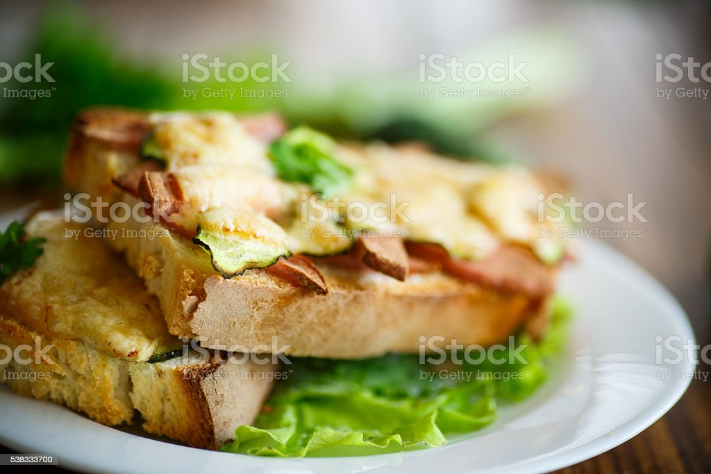 toast baked with sausage, cheese and cucumber stock photo