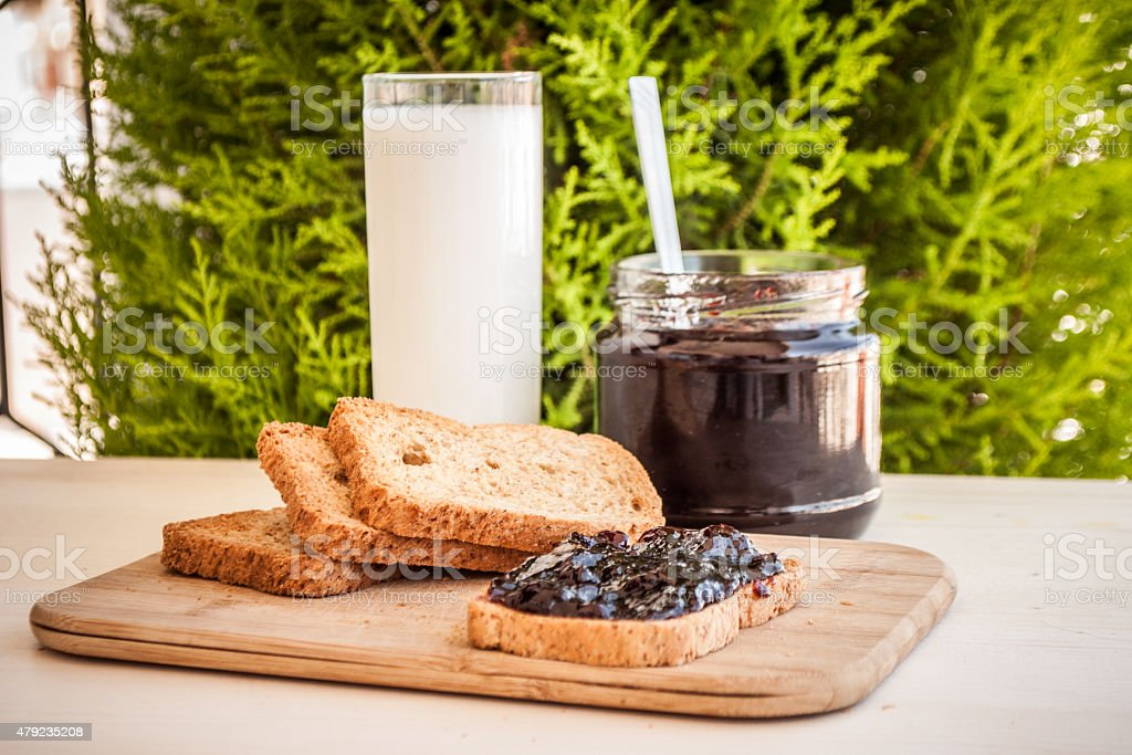 toast bread with marmelade and a glass of milk stock photo