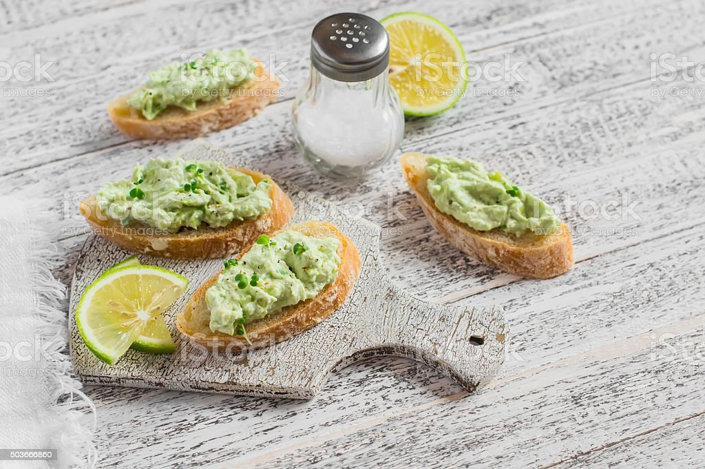 Toast with avocado and cream cheese on a white board. stock photo