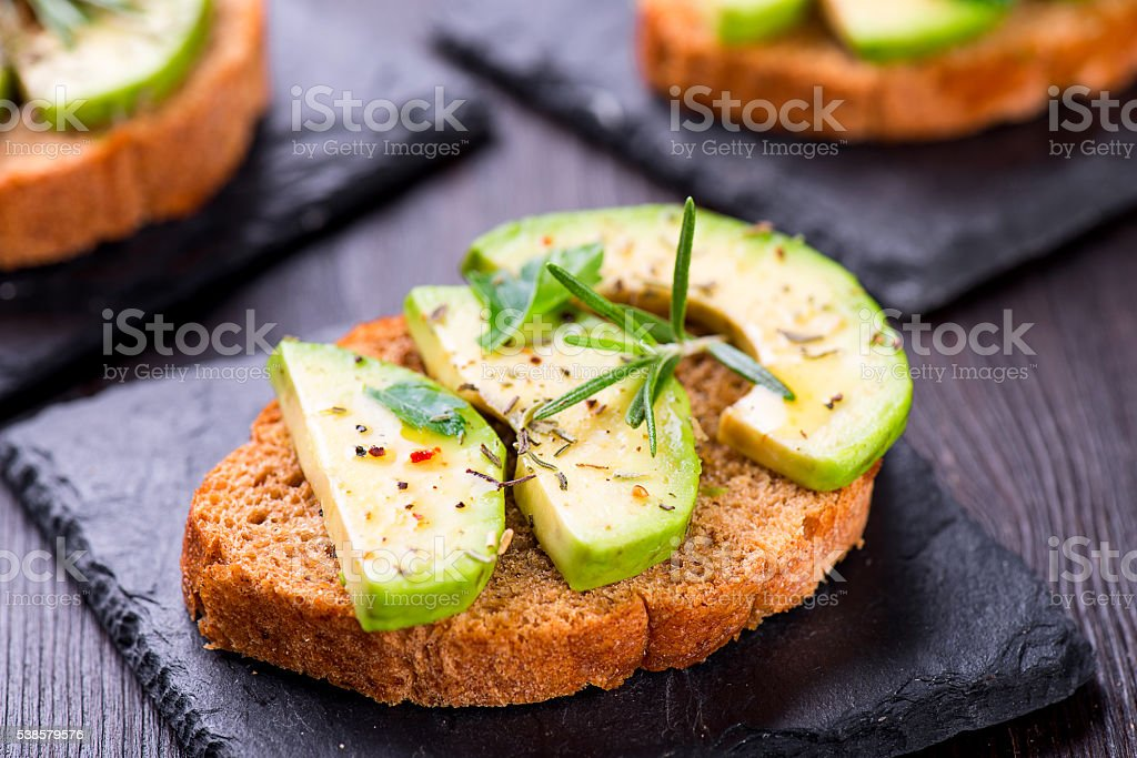 Toast with avocado, herbs on slate board stock photo