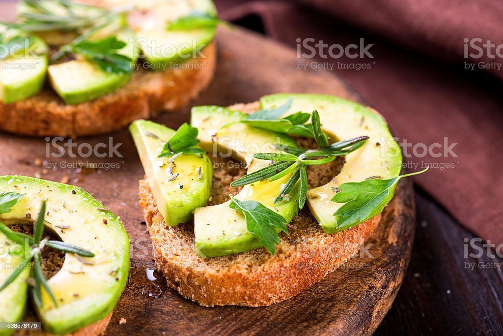 Toast with avocado, herbs on wooden board stock photo