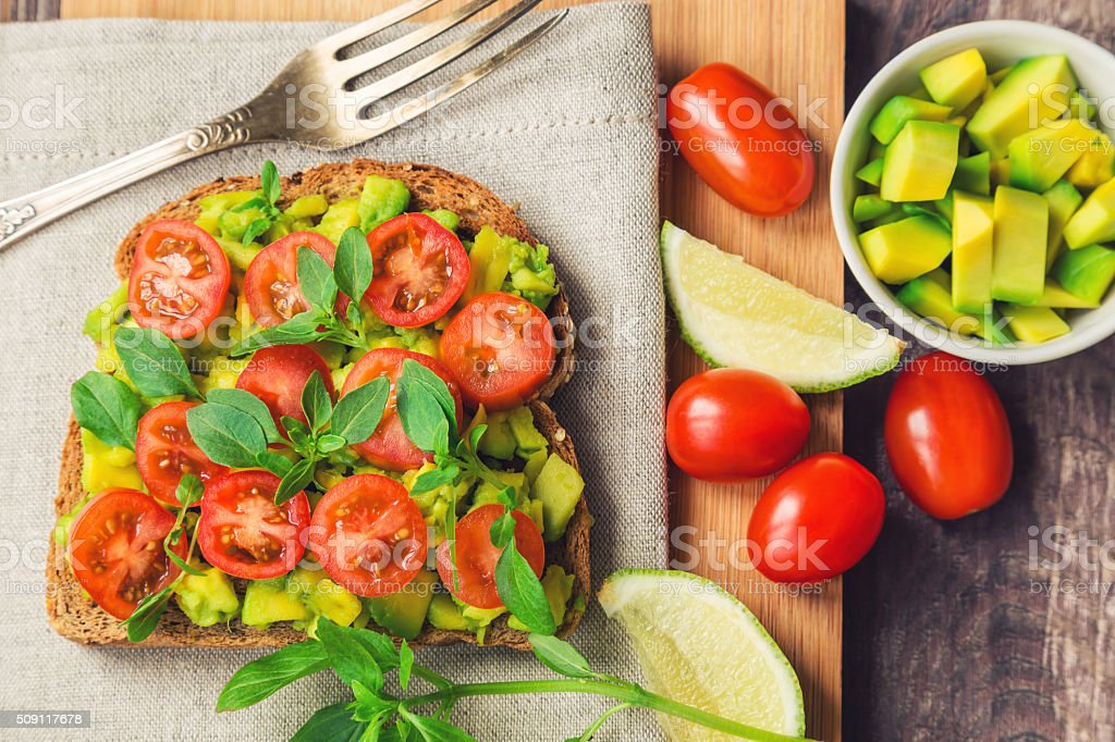Toast with avocado, tomatoes and basil stock photo
