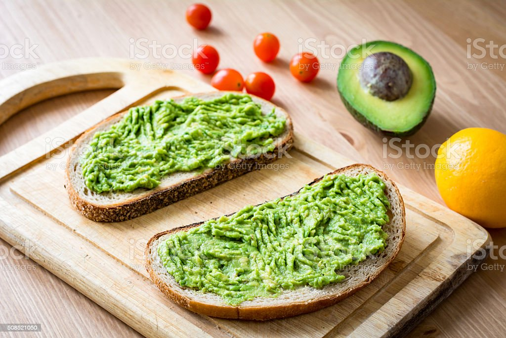 Toast with mashed avocado on wooden cutting board stock photo