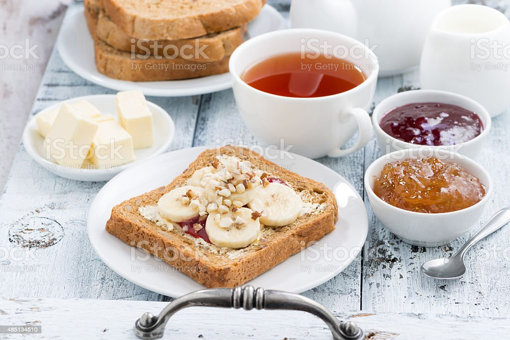 toast with peanut butter and banana, fresh black tea stock photo