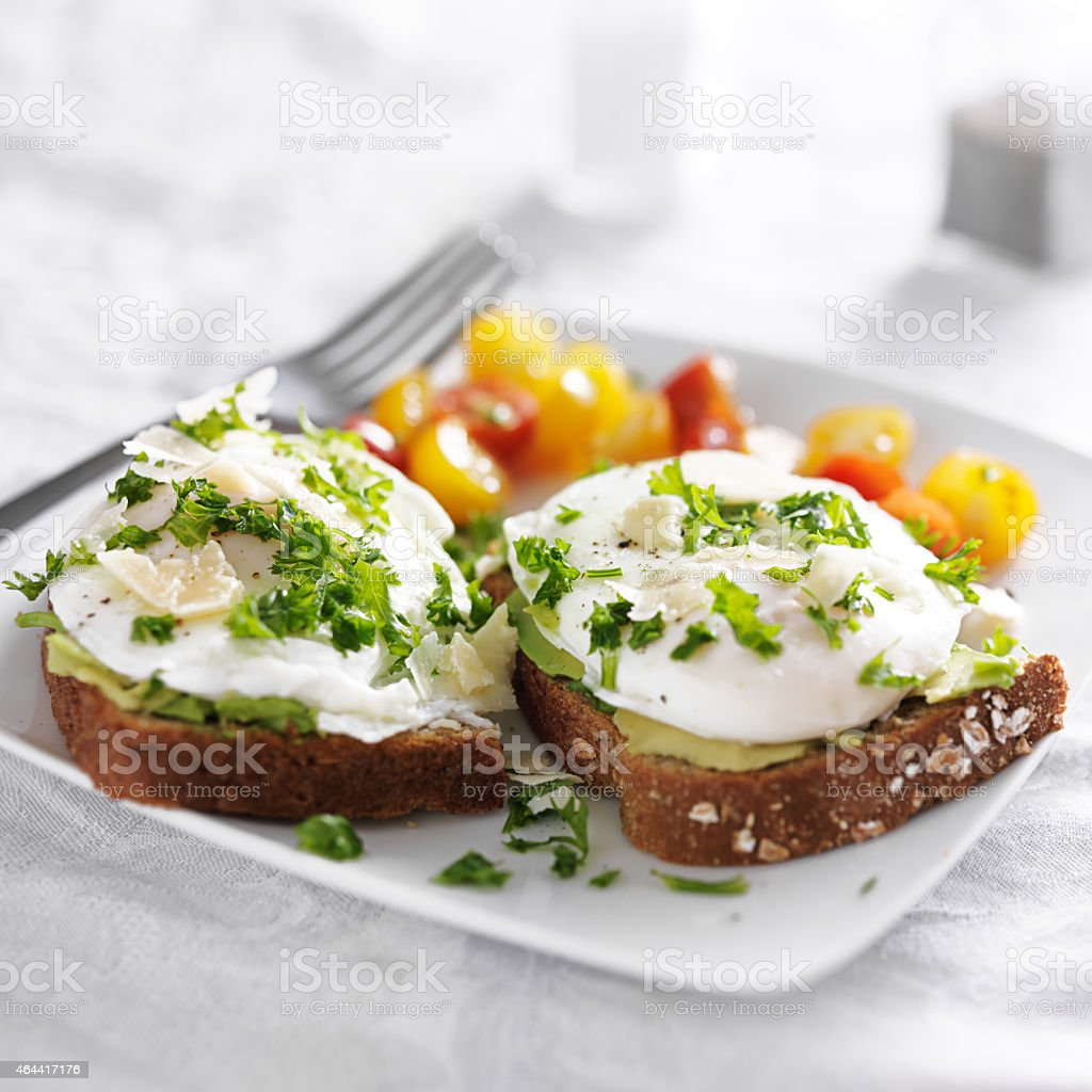 toast with poached eggs, avocado and tomatoes stock photo