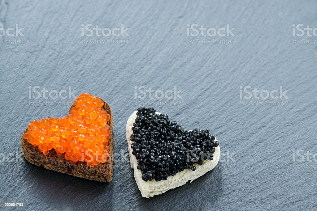 toast with red and black caviar in heart-shaped stock photo