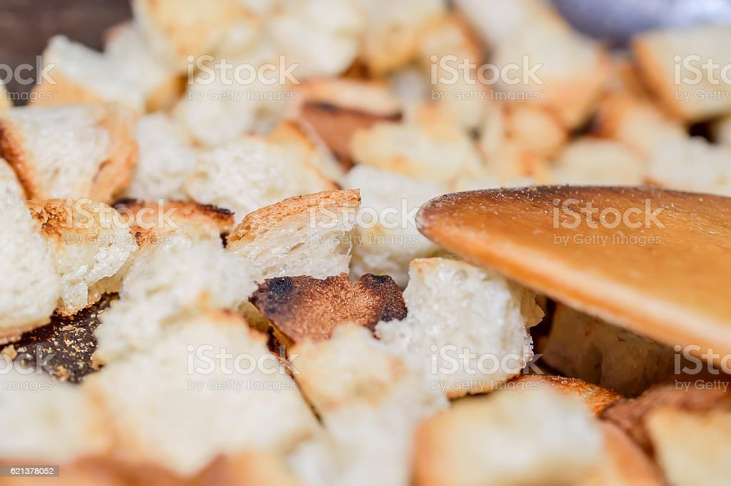 Toasted bread cubes with spatula close up stock photo