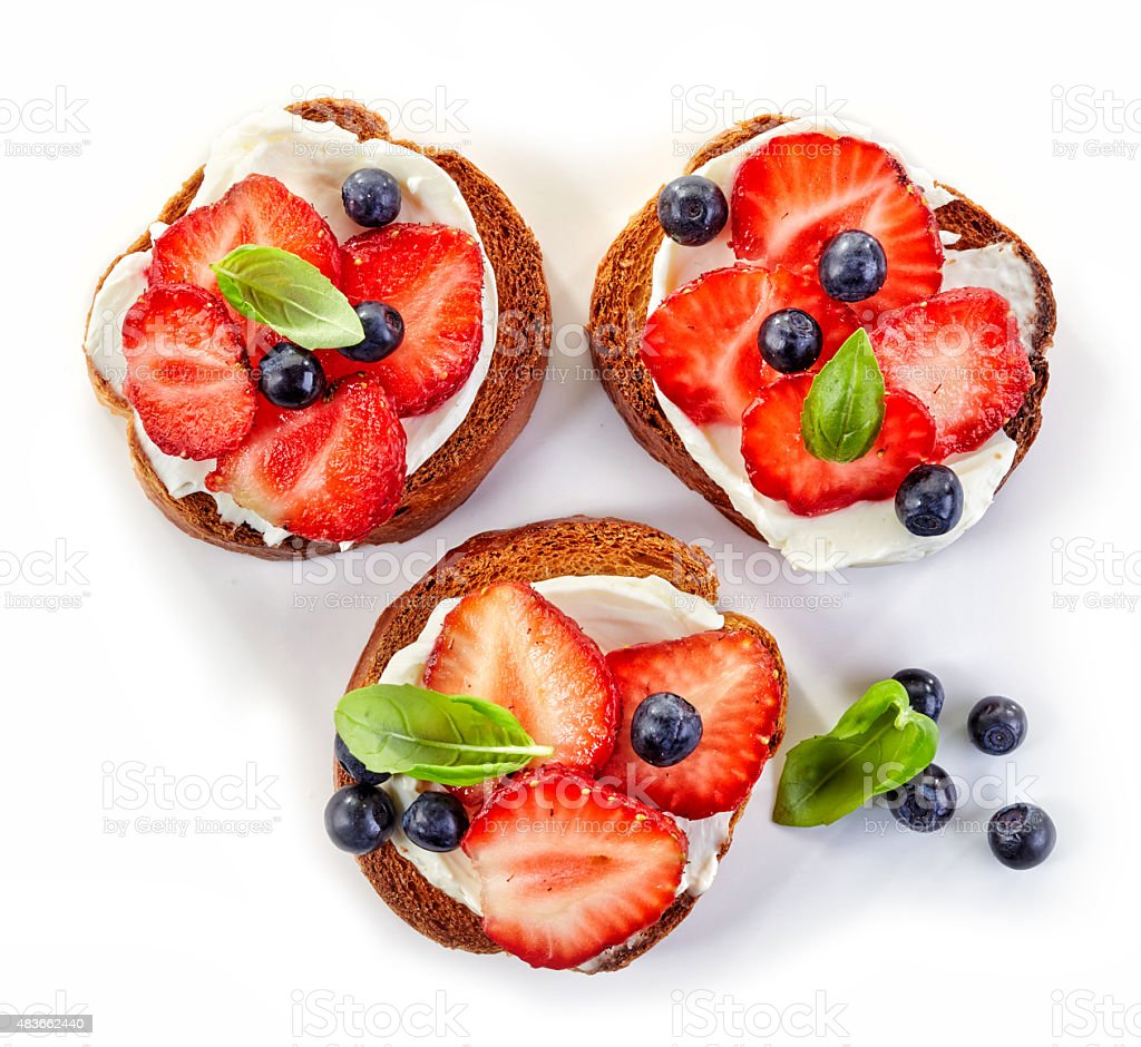 toasted bread with cream cheese and berries stock photo