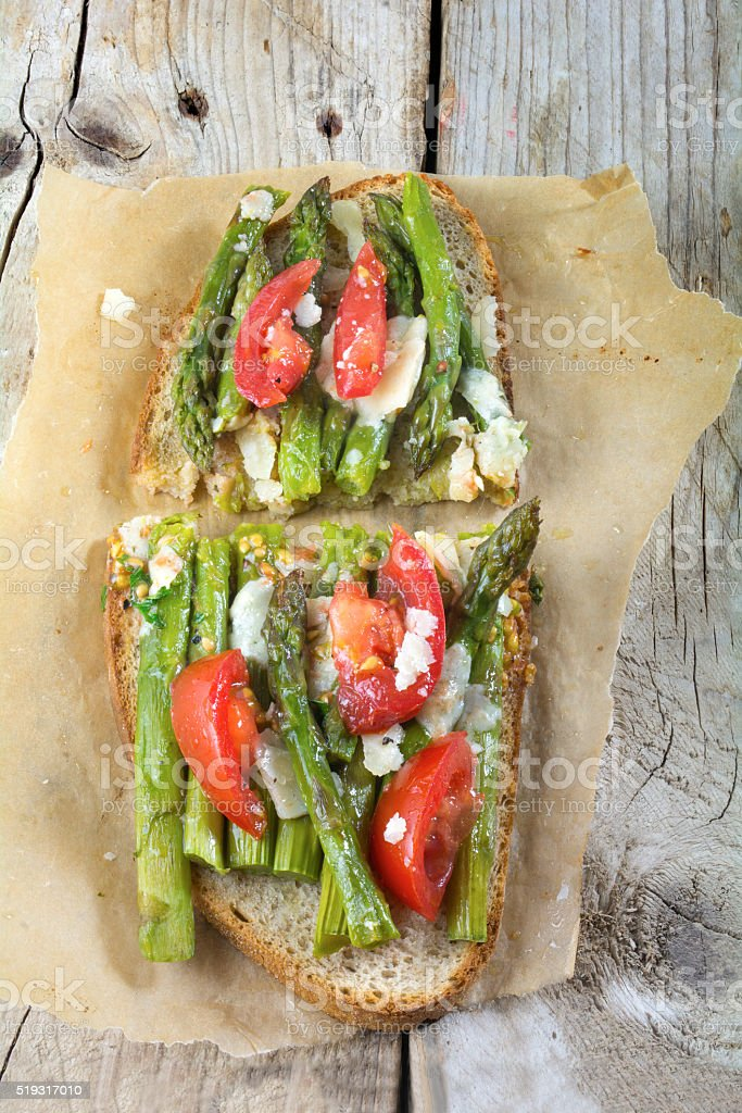 toasted bread with green asparagus, tomatoes and parmesan from above stock photo