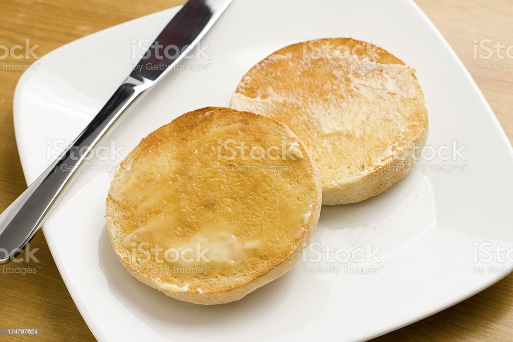 Toasted English muffins with melting butter on a plate royalty-free stock photo