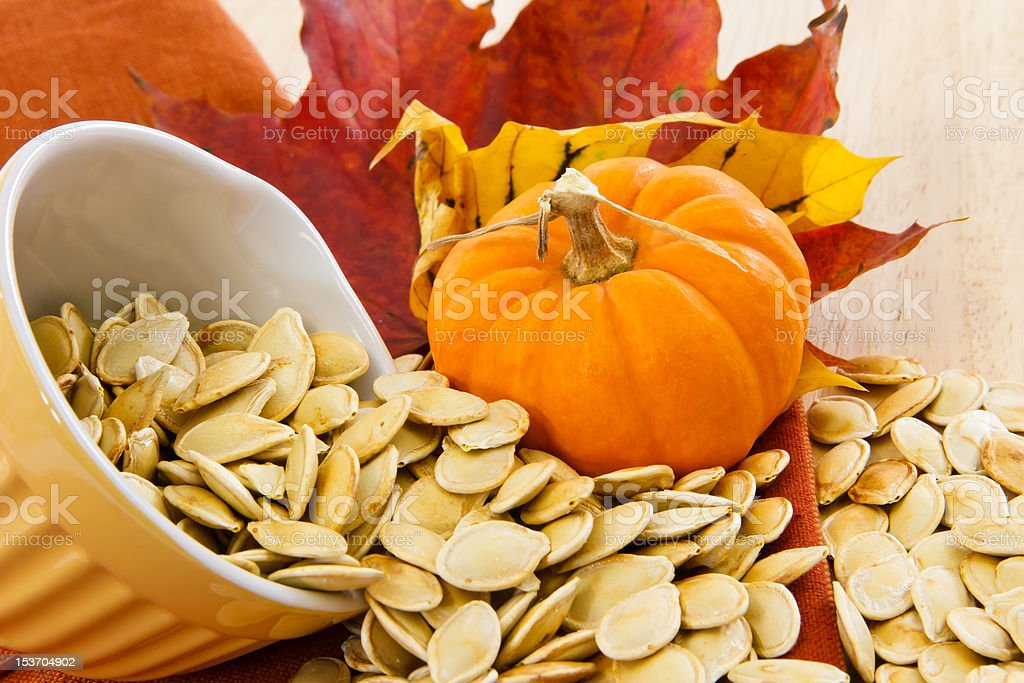 Toasted pumpkin seeds spilling from a yellow bowl stock photo
