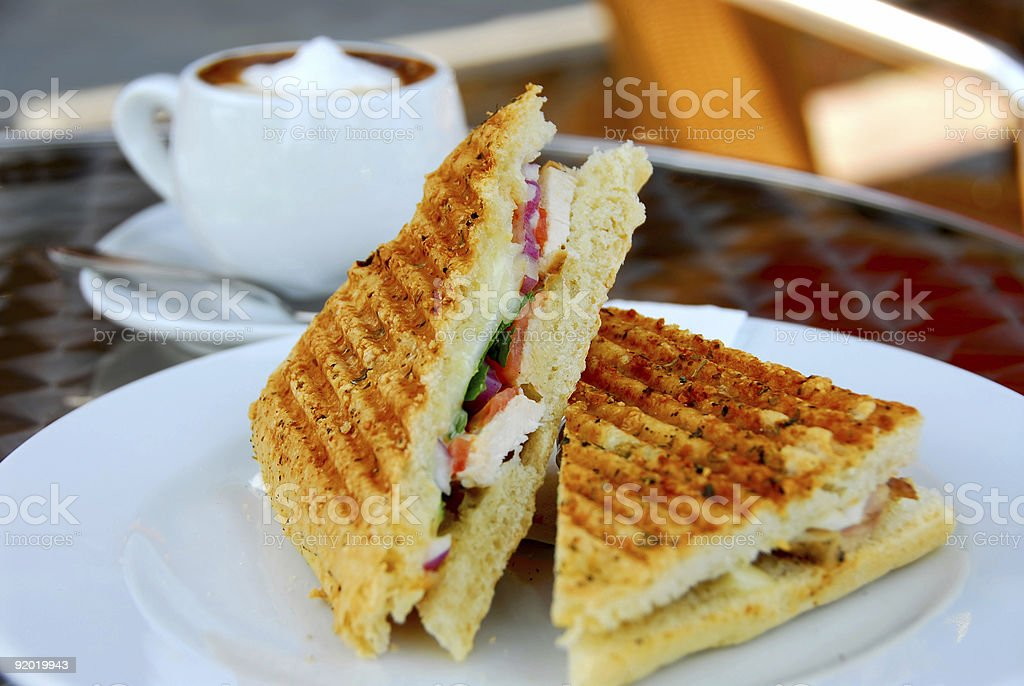 Toasted sandwiches on a plate in front of teacup of coffee stock photo